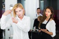 Den negativa klienten grälar med barberaren Royaltyfria Foton