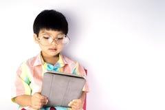 Den Nerdy asiatiska pojken läser på minnestavlan fotografering för bildbyråer
