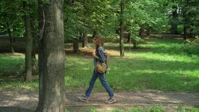 Den Nerdy högskolestudenten med långt lockigt hår som in går, parkerar och framåtriktat omkring ser, träd och gräs, solsken arkivfilmer