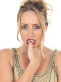 Den nervösa skrämda stickande tummen för den unga kvinnan spikar Royaltyfria Foton