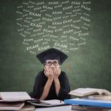 Den nervösa studenten med kappan förbereder examen Arkivbilder