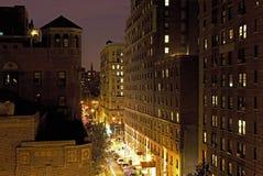 Den New York City gatan och hus höjde sikt på natten Arkivfoton