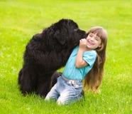 Den Newfoundland hunden kysser en flicka Arkivfoto