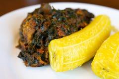Den nigerianska kokta pisanget tjänade som med en kryddig grönsaksås arkivbild