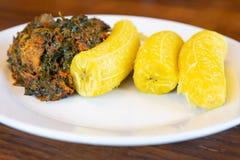 Den nigerianska kokta pisanget tjänade som med kryddig grönsaksoppa Arkivbilder