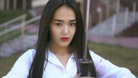 Den Ninja flickan ser bladet av hennes katana Vind blåser folkets brunetthår lager videofilmer