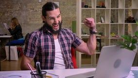Den njutbara caucasian mannen med det svarta skägget skrattar, medan se hans dator och skriva och att ha gyckel på arbetsplats stock video