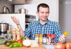 Den normala grabben väljer kryddor i köket hemma Royaltyfria Bilder