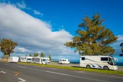 DEN NORR ÖN, NYA SJÄLLAND MAY 18, 2017: Några bussar parkerade nästan hamnplatsen och loveleysikt av sjön Taupo med Royaltyfri Foto