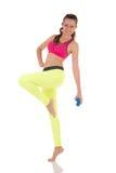 Den nätta brunettkvinnan som gör komplexet, övar för muskler tillbaka, ben, bakdelar och händer genom att använda blåa hantlar Royaltyfria Bilder