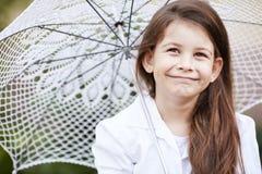 Den nätta flickan med snör åt paraplyet i den vita dräkten Arkivfoton