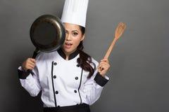 Den nätta kvinnakocken har gyckel med hennes matlagninghjälpmedel Arkivbilder