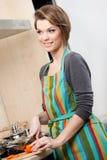 Den nätta kvinnan i randigt förkläde lagar mat grönsaker Arkivfoto