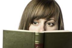 Den nätta kvinnliga studenten läser en bok Arkivfoto
