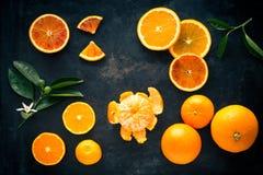 Den nya apelsinen bär frukt och skivor på ett svart metallmagasin royaltyfri bild