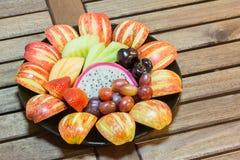 Den nya blandningen bär frukt i svart platta på den wood tabellen Royaltyfria Foton