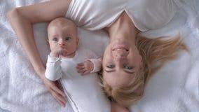 Den nya familjen, siktsöverkant på attraktiv moder med trevligt nyfött behandla som ett barn flickan som ligger på det vita sängs arkivfilmer