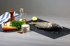Den nya fisken kverulerar med citrus- och grönsakingredienser på trätabellen som lagar mat matbegrepp arkivbilder