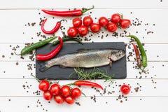 Den nya forellfisken på svart kritiserar skärbrädan med körsbärsröda tomater Fotografering för Bildbyråer