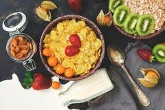 Den nya frukosten av cornflakes, mjölkar, jordgubben, kiwin och muttrar på en mörk stenbakgrund Bästa sikt, lekmanna- lägenhet Sp arkivbild