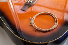 Den nya gitarren stränger pålagt den akustiska gitarren Royaltyfri Fotografi