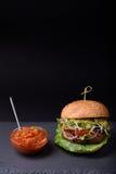Den nya hemlagade hamburgaren med tomat- och zucchinizucchinisås kritiserar på brädet Mörkt bakgrunds- och kopieringsutrymme Royaltyfri Foto