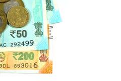 Den nya indiern 50 och 200 rupier med 10 och 5 rupier mynt på vit isolerade vit bakgrund Fotografering för Bildbyråer