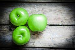 Den nya lantgården lyftte äpplen på lantlig träbakgrund Arkivfoto