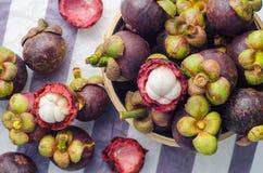 Den nya mangosteenen bär frukt i korgen på pappers- bakgrund Arkivfoton