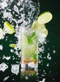 Den nya mojitodrinken med flytandefärgstänk och krossad is i frysning vinkar fotografering för bildbyråer