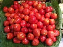 Den nya organiska lilla tomaten står ut bland många tomaten på banantjänstledigheter med suddighetsbakgrund i korg i supermarket  Arkivfoto