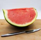 Den nya skivade vattenmelon på trätabellen, vit bakgrund, försilvrar kniven fotografering för bildbyråer