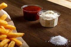 Den nya stekte fransmannen steker med ketchup på träbakgrund Arkivfoton