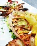 Den nya tioarmade bläckfisken med potatisen steker på en grekisk krog royaltyfria foton