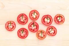 Den nya tomaten klippte halva med rosmarinbladet som en klocka Världsklocka Arkivbilder