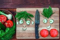 Den nya tomater och gurkan i en bunke och på ett kök stiger ombord Royaltyfria Foton