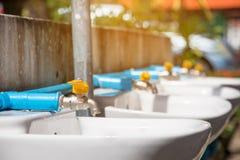 Den nya vattenkranen, ändrar den plast- vattenkranen och blassvattenkranen i skola Arkivbild