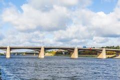 Den nya Volga bron och stadskajen i Tver, Ryssland Pittoreskt flodlandskap bluen clouds skyen narrow för lawn för green för djupf royaltyfria foton