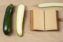Den nya zucchinin och anteckningsboken som ligger på en säckväv, ytbehandlar Arkivbilder