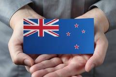 Den nyazeeländska flaggan gömma i handflatan in Royaltyfri Foto