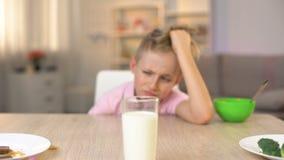 Den nyckfulla manliga ungen som SAD ser exponeringsglas av, mjölkar på köksbordet, sunt mål arkivfilmer