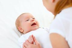 Den nyfödda framsidan behandla som ett barn i armar av modern Arkivfoton