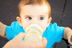 Den nyfödda Give matningsflaskan behandla som ett barn royaltyfri bild