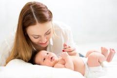 Den nyfödda lyckliga modern som rymmer, behandla som ett barn handen Royaltyfri Foto
