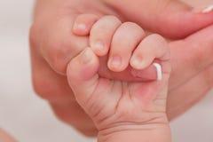 Den nyfödda modern som rymmer, behandla som ett barn handen för ` s Royaltyfri Fotografi