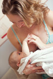 Den nyfödda modern som rymmer, behandla som ett barn och att amma Arkivfoton