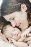 Den nyfödda modern som rymmer, behandla som ett barn tätt royaltyfria bilder