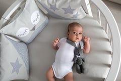Den nyfödda pojken ligger i en rund säng Royaltyfri Foto
