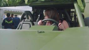 Den nyfikna kvinnan är på hjulet av den militära bilen Hon ler lyckligt lager videofilmer