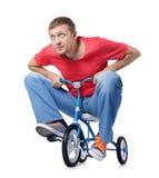 Den nyfikna mannen på barns cykel arkivfoto